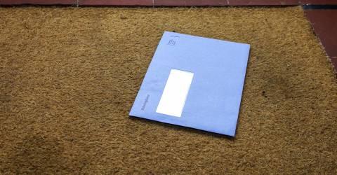 Blauwe envelop van de Nederlandse belastingdienst op de deurmat, Prinsjesdag, Belastingen, Miljoenennota