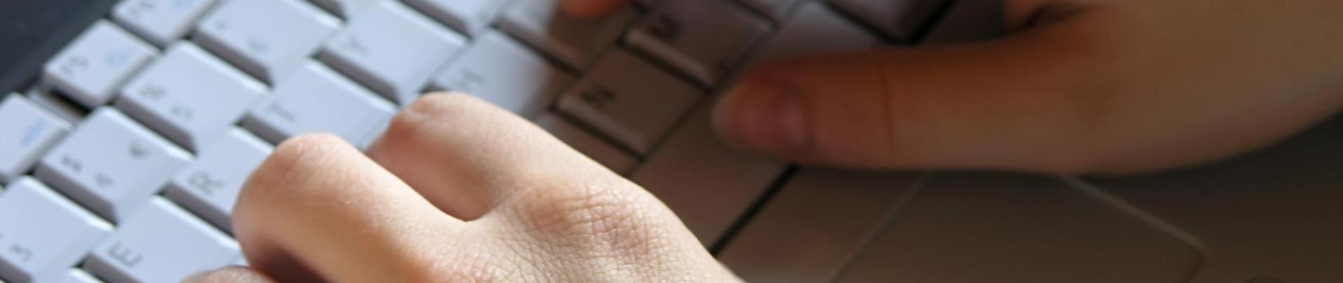 twee handen aan het typen op grijze laptop