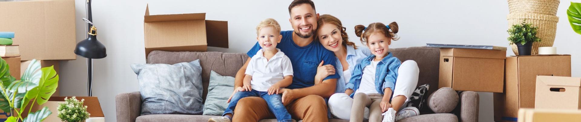 Gelukkig gezin vader moeder en kinderen verhuizen en pakken dozen uit